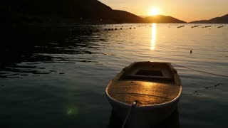 Footage of a small wooden boat swinging on a sea, filmed during a sunset...