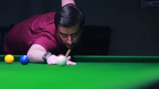 Footage of a snooker player hitting the ball, he misses the hole, the shot moves...
