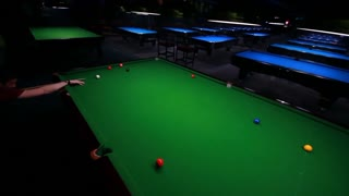 Footage of a snooker player in an entertainment club playing snooker, the shot is moving from left to right while the player hits the ball...