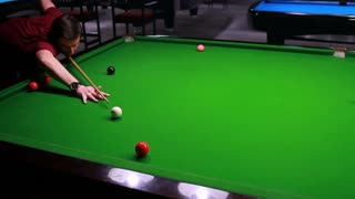 Footage of a snooker player, the shot is moving from left to right while the player hits the ball and it goes in...