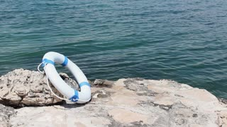 Footage of a stone pier and a white buoy leaned on a stone