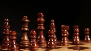 Footage of a white king being put in front of the white peaces on a chess board, isolated on black background...