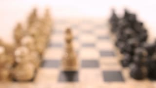 Footage of a white king standing between two lined up chess peaces, the shot comes from out of focus into focus...