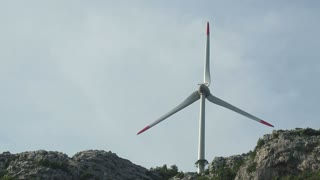 Footage of a windmill on a mountain producing energy...