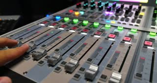 Footage of an audio mixer in a recording studio, a man is adjusting the output audio on it and the shot is moving from left to right...