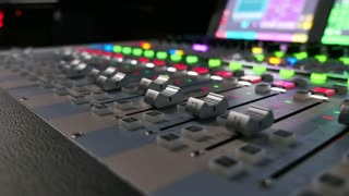 Footage of an audio mixer, the shot moves from the right to the left, the knobs are being pulled up and down automatically...
