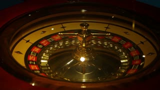 Footage of a casino roulette - the spinning ball stops at a red number...