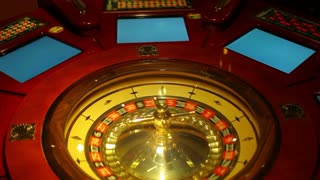 Footage of a casino roulette - the spinning ball stops at black fifteen...
