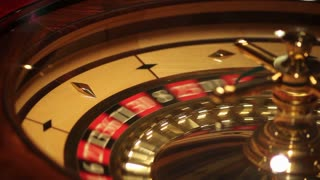 Footage of a casino roulette - the spinning ball stops at red 36...