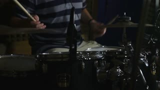 Footage of a man playing and practicing drums in a recording studio...