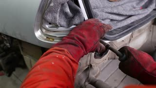 Footage of a man welding a part of the car and preparing it for a general repair...