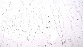 Footage of heavy rain falling down a window...