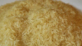 Footage of rice on a plate and a person is checking the quality of the rice...