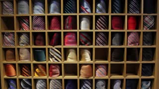 Front shot of a tie collection - a man picking up a tie for his shirt