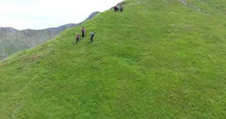 Group of hikers going down the mountain, aerial footage...