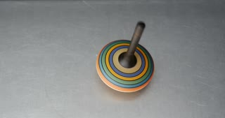 High shot of a colorful spinning top on a metal table...