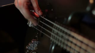 in a recording studio - a man playing on his black bass guitar