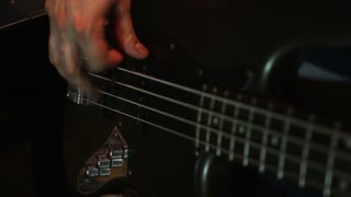 In a recording studio - a man playing on his black bass guitar...