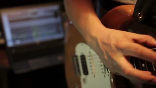 Footage of a man playing on his electric guitar in a recording studio with a laptop in the background...