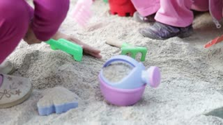 Kids playing with children's toys in sand...