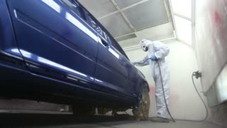 Low angle footage of a car painter - painting a blue car...