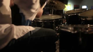 Low angle footage of a man playing drums at a concert...