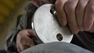 Low angle footage of a metal worker grinding a hole in a metal part...