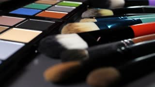 Low angle shot of a make up palette and some brushes next to it, the shot is moving...