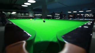 Low angle shot of a snooker table and a player hiting the ball...