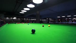 Low angle shot of a snooker table and a player hitting the ball