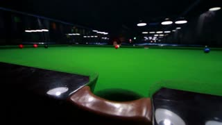 Low angle shot of a snooker table and a player receives one point, the shot approaches the middle hole and moves to the right...
