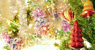 Part of a Christmas tree with some decorations on it with a colorfull background, the shot moves from the bottom to the top