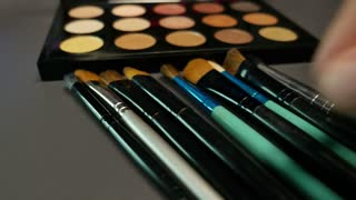Several brushes lying in front of a professional make-up palette, the shot is moving in a half circle and a person takes a brush and uses a color...