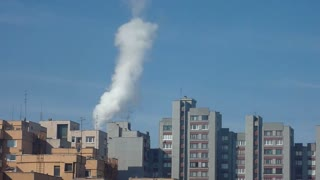 Shot of two buildings being heated by a close heating plant...