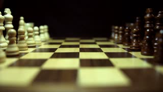 Side and wide angle shot of a chess board and the chess peaces lined up. A person is opening the game with the pawn...