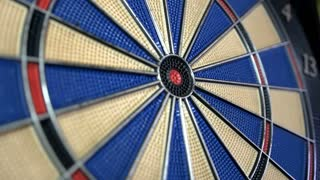 Side angle shot of a dart board and a person hitting the bullseye...