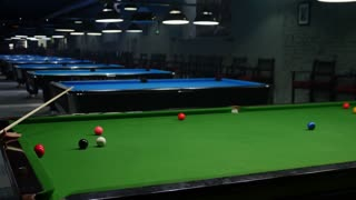Side shot of a snooker game and a player enjoying in a snooker game in an entertainment center...