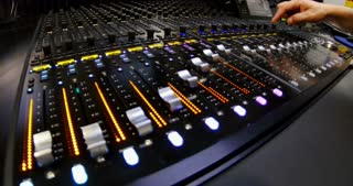Side shot of an audio mixer and a man putting it into demo mode, the knobs are being pulled up and down automatically...