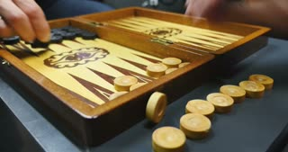 Side shot of two people playing the backgammon...