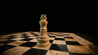 Slow motion footage of a chess board and two kings on it, the black king throws down the white king and replaces his place...