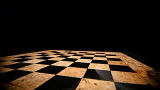 Slow motion of a person rotating a white king chess piece on a chess board...