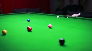 Snooker table and a player enjoying the game, the shot moves from left to right...