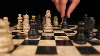 The end of a chess game, a person hits the white king with a black queen and throws the king down on the chess board...