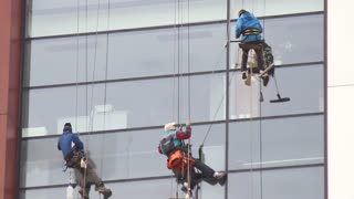 Three freelancers cleaning the windows on a high building...