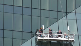 Three man imbedding a huge glass window into a new modern building.