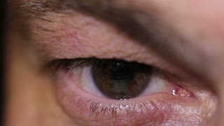 Time Lapse of a human eye reading something on a tablet, there is a reflection in his eye