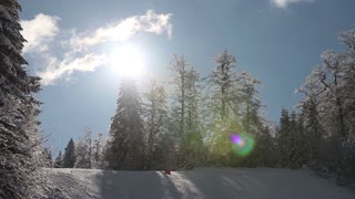 Time lapse of a winter scene and a ski slope at a mountain - skiers are passing by