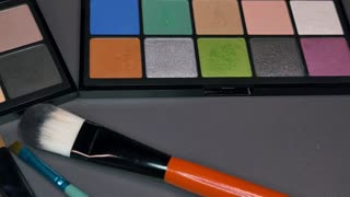 Two make-up palettes standing next to each other with some brushes in front of them, the shot is moving from right to left...