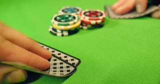 Two players playing black jack, they put some chips on the table and reveal their cards