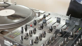 A DJ changes the vinyl and starts to mix music